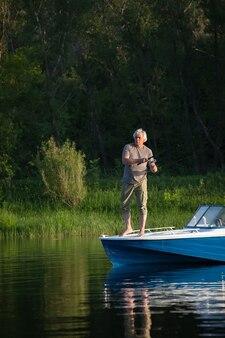 Зрелый мужчина на моторной лодке. ловит рыбу.