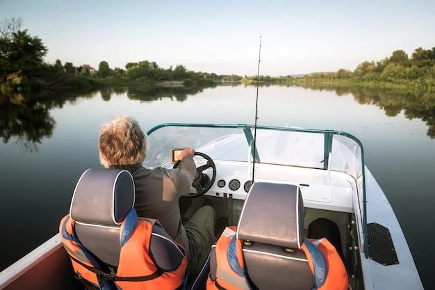 Зрелый мужчина на моторной лодке. рыбная ловля.