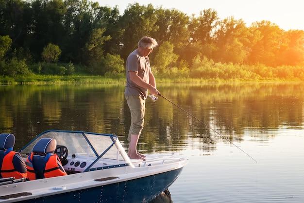 Зрелый мужчина на моторной лодке. ловит рыбу