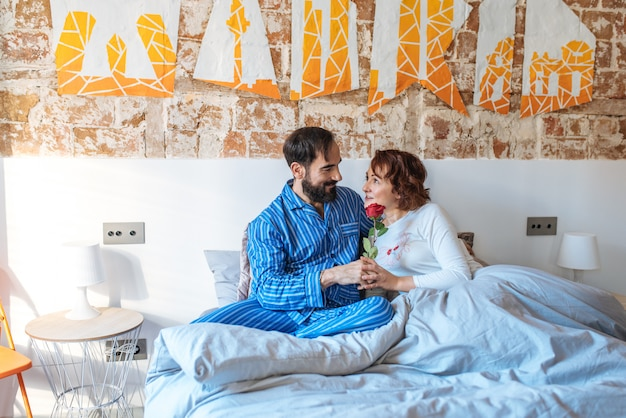 Зрелый мужчина на пижаме дарит розу на день святого валентина, чтобы ее жена отдыхала дома в постели