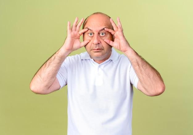 成熟した男がオリーブグリーンの壁に隔離された指で目を開く