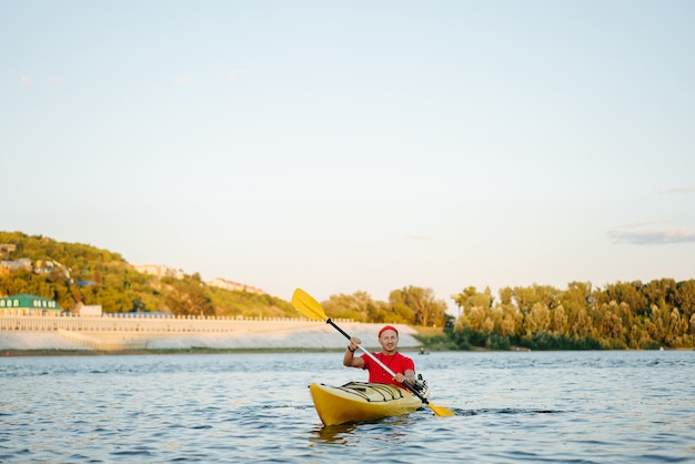 Mature man in orange watch cap riding on yellow kayak on a big wide river. reinforsed shoreline and trees in a distance.