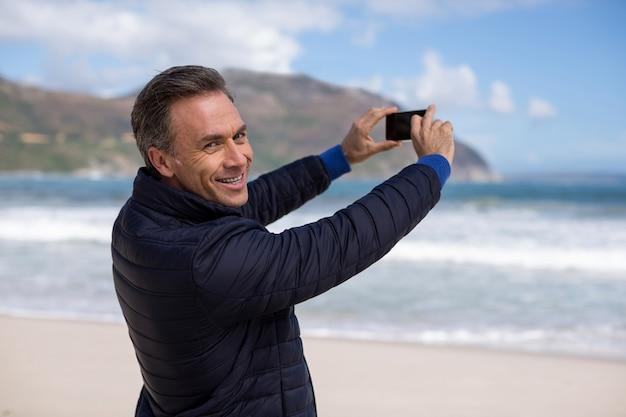 Зрелый человек фотографирует пейзаж с помощью мобильного телефона на пляже