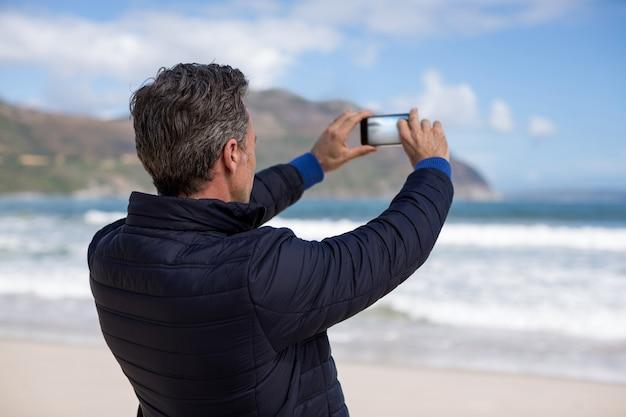 Зрелый человек фотографирует пейзаж с помощью мобильного телефона