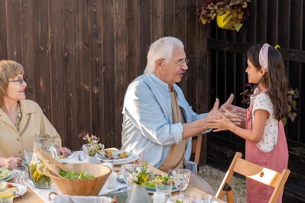 Зрелый мужчина играет с внучкой за сервированным столом