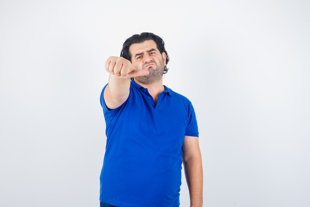 Mature man pointing aside with thumb in blue t-shirt looking disappointed, front view.