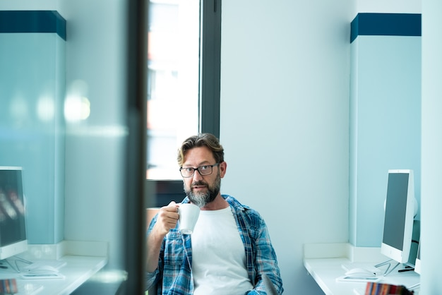 オフィスでコーヒーを飲みながらカメラを見ている成熟した男の肖像画-コンピュータコンセプトのライフスタイルとフリーランスのオンラインジョブ-コワーキングスペースの大人の白人の人々-青い気分は現代の人々を彩る