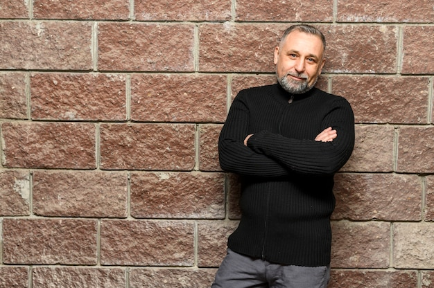 Mature man posing next to brick wall with copy space
