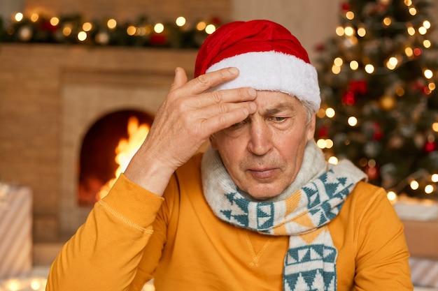 Зрелый мужчина позирует в помещении против камина и украшенной елки