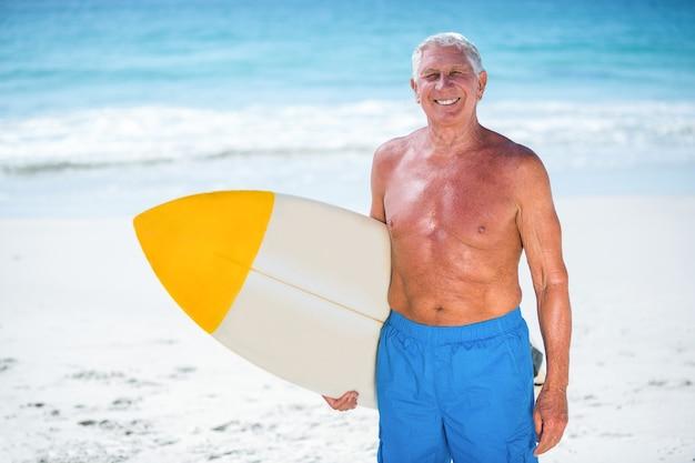 Зрелый мужчина позирует с доской для серфинга