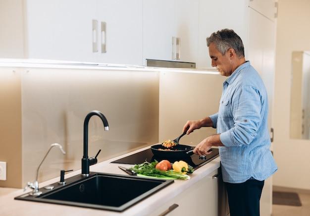 Зрелый мужчина готовит здоровую пищу на ужин для своей семьи