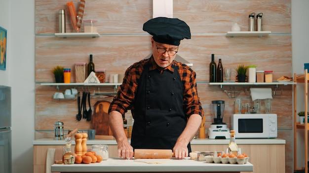 Зрелый мужчина готовит домашнюю пиццу на домашней кухне. счастливый пожилой шеф-повар с bonete, используя деревянную скалку, замешивая сырые ингредиенты для выпечки традиционного печенья, посыпая, просеивая муку на столе.
