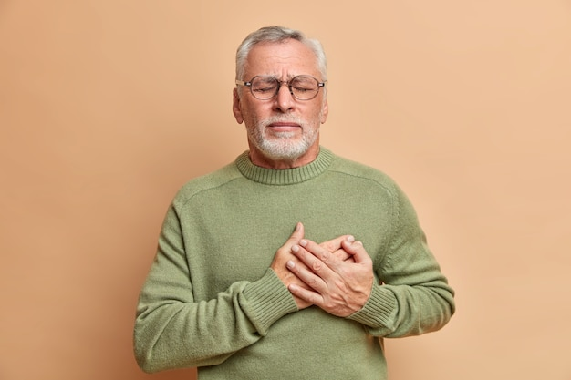 Mature man presses hands to heart has cardio problems suffers heart attack and chest pain stands with closed eyes needs doctors help wears casual jumper isolated over brown wall