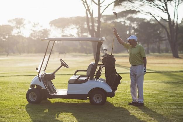 Mature man putting golf club in bag