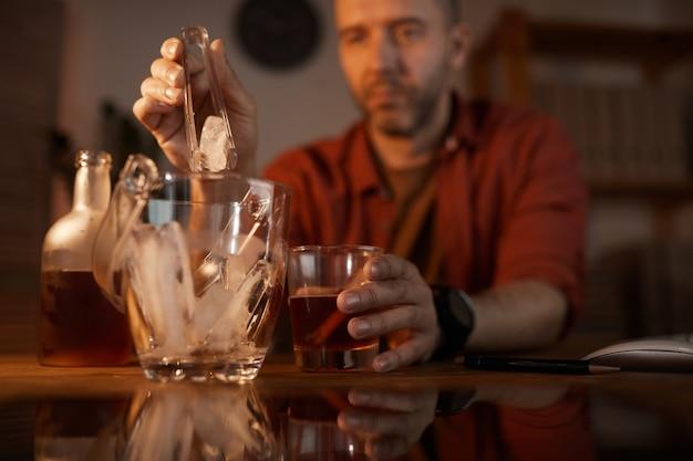 Зрелый мужчина кладет лед в стакан с алкоголем, сидя за столом дома