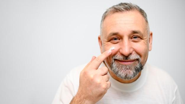 Uomo maturo che mette la crema per la cura della pelle sul suo fronte