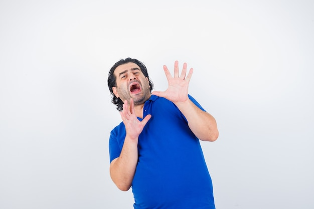 青いtシャツで停止するために手を上げる成熟した男、怖い顔、正面図。