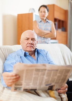 Mature man reading newspaper against sad woman