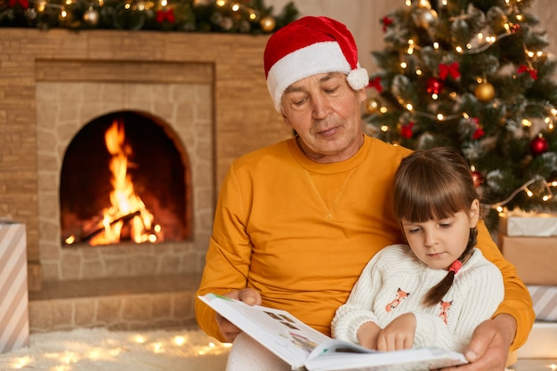 Mature man reading story with his granddaughter in living room decorated with christmas tree and garlands, child and grandfather sitting near fireplace and looking attentively at pages of book.
