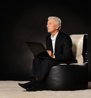 검은 배경에 노트북과 함께 편안한 성숙한 남자