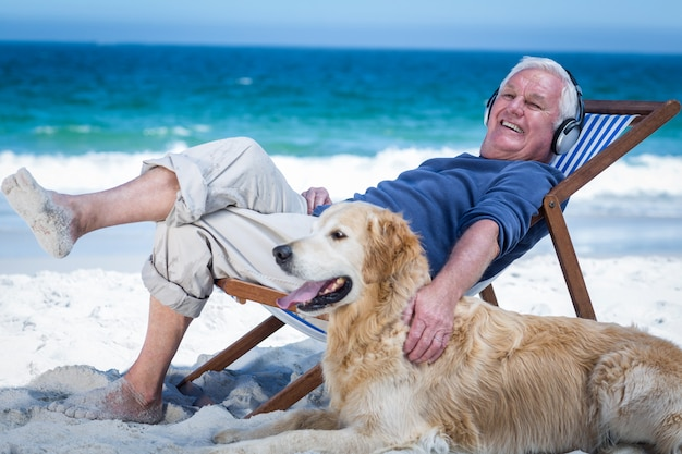 Mature man resting on a deck chair listening to music petting his dog