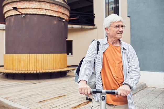 Зрелый мужчина катается на скутере в городе