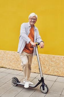 Зрелый мужчина на скутере на желтом