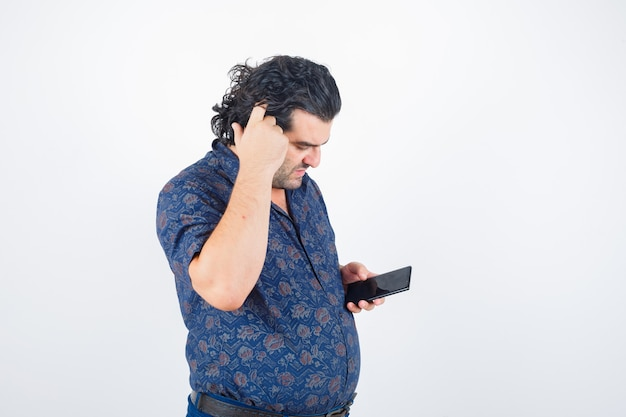 Mature man scratching head while holding mobile phone in shirt and looking thoughtful. front view.