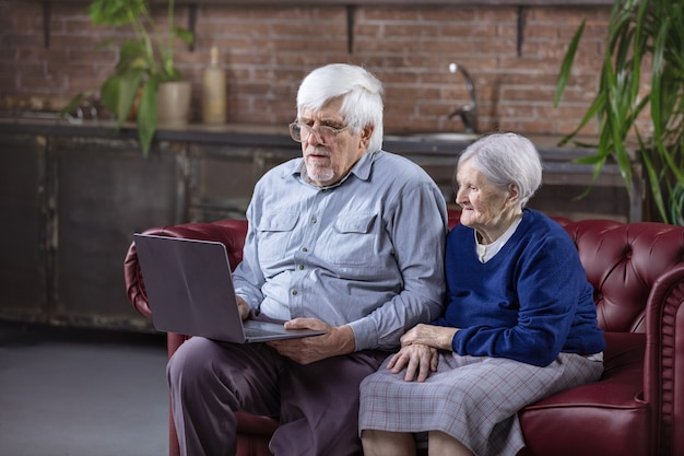 Mature man and senior woman using laptop while sitting on couch. watching video or surfing web on laptop.