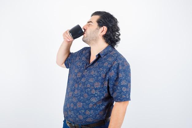Uomo maturo in camicia che beve e che sembra felice, vista frontale.
