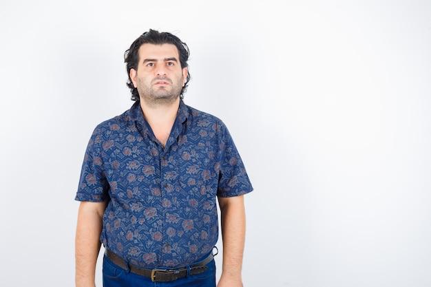 Uomo maturo in camicia che guarda lontano mentre posa e guardando fiducioso, vista frontale.