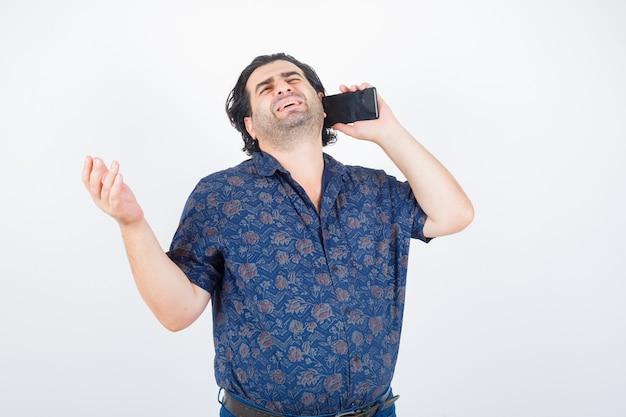 Uomo maturo in camicia parlando al telefono cellulare e guardando malinconico, vista frontale.