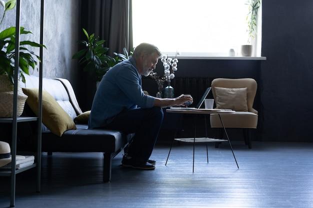 집에서 신용 카드를 사용하여 노트북으로 온라인 쇼핑을 하는 성숙한 남자.