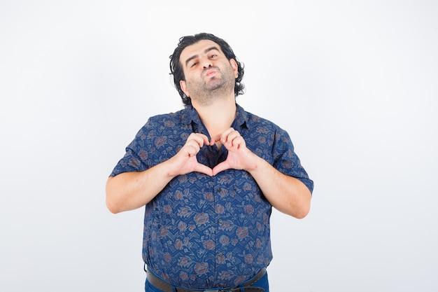 Зрелый мужчина показывает жест сердца, надувая губы в рубашке и выглядит довольно. передний план.