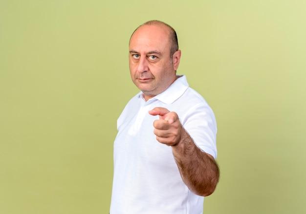 Uomo maturo che ti mostra gesto isolato sulla parete verde oliva