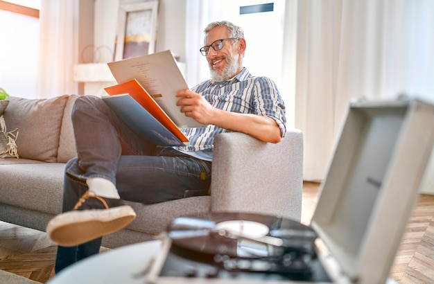 A mature man sits on the couch at home, relaxes, enjoys life and listens to vinyl records on a music player.