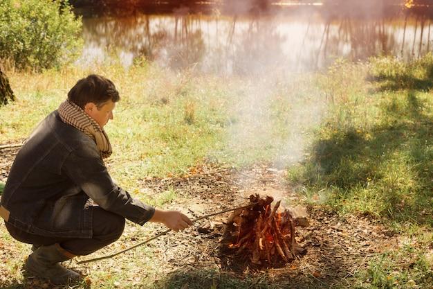 キャンプファイヤーに座っている中年の男性