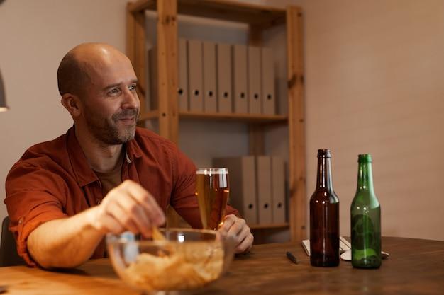 Зрелый мужчина сидит за столом и пьет пиво с чипсами, отдыхает после работы