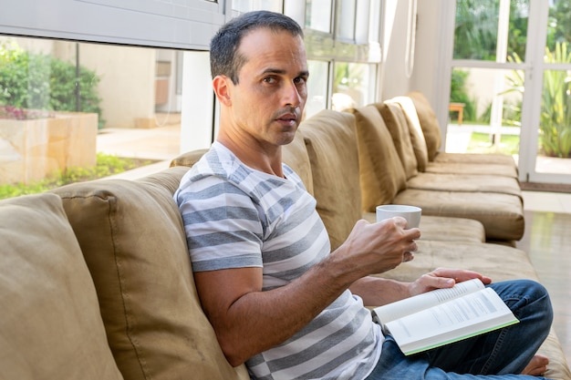 Mature man sitting on the couch, drinking coffee and reading a book.