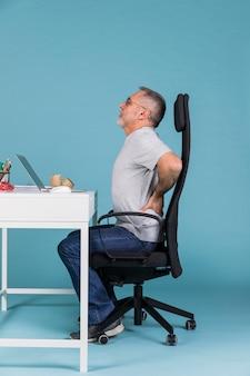 Зрелый человек, сидя в кресле, страдает от боли в спине при использовании на ноутбуке