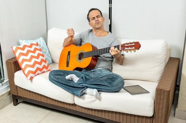 Зрелый мужчина сидит на диване и с чувством играет на гитаре.