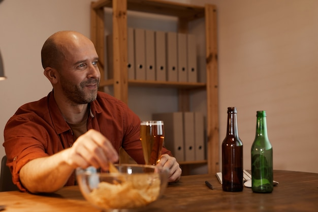 Mature man sitting at the table and drinking beer with chips he resting after work