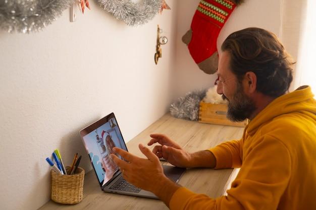 成熟した男性の笑顔と陽気な女性を呼び出して、ワイヤレスインターネット接続を備えたラップトップコンピューターでビデオ通話会議アプリケーションを使用して一緒にクリスマスを祝う-現代のお祝いオンライン
