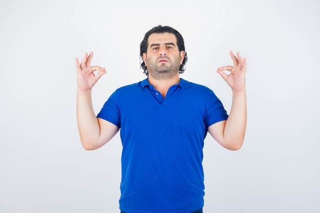 Mature man standing in meditating pose in blue t-shirt, jeans and looking relaxed