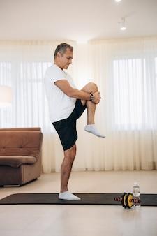 片足で立って別の足を伸ばす中年の男性