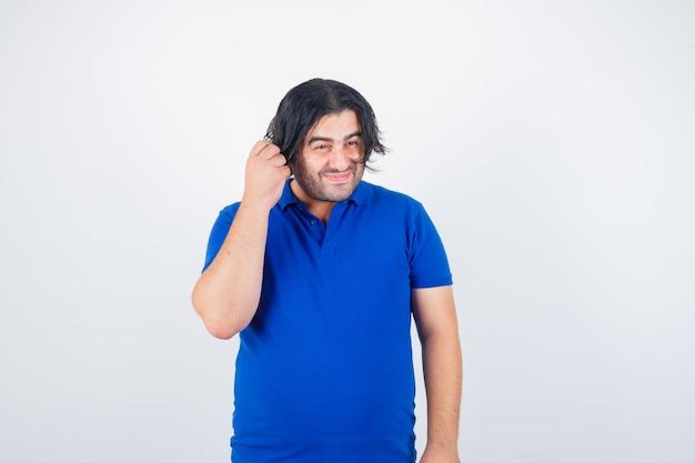 Uomo maturo in piedi dritto, sorridente in maglietta blu, jeans e guardando allegro, vista frontale.