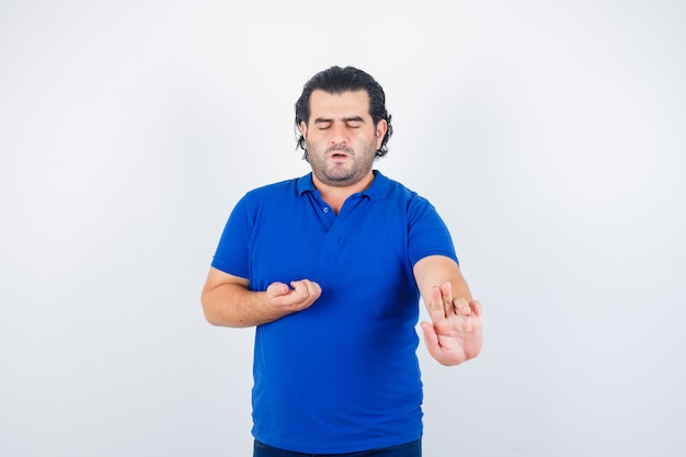 Mature man stretching hand as holding something in blue t-shirt and looking calm
