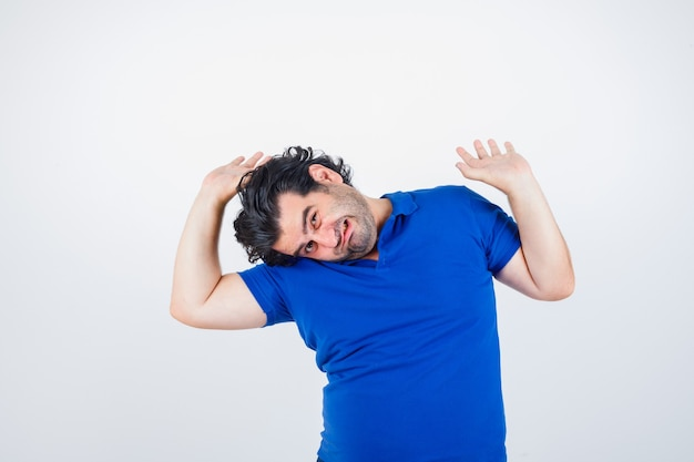 Mature man stretching hands as holding something imaginary, grimacing in blue t-shirt, jeans and looking exhausted , front view.