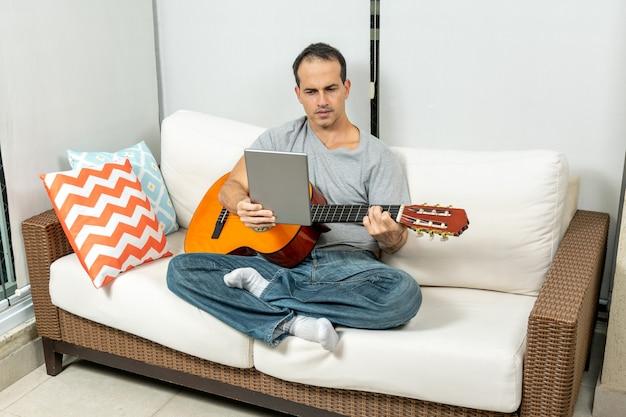 Зрелый мужчина изучает музыку на планшете и практикует на гитаре