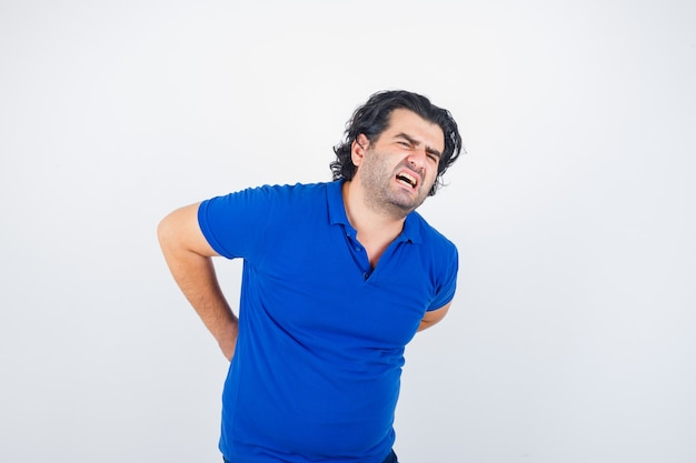 Mature man suffering from backache in blue t-shirt and looking fatigued , front view.